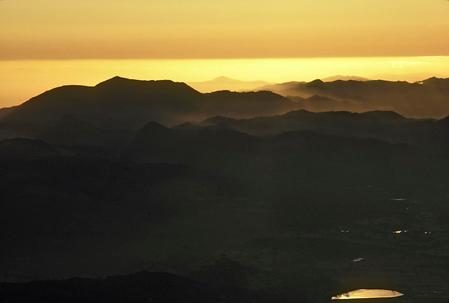 Vaca Mountains northeast of Napa, California, silhouetted against hazy sunset of mid-Napa Valley.  Camera faces west.