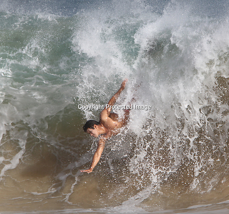 Body surfing at Sandy's Beach takes some skill to stay upright in the dangerous beach break of  the high waves.