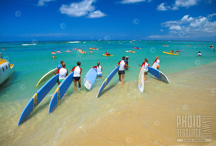 People on vacation ( girls and children) learn the techniques of surfing from a qualified instructor on waikiki beach, Oahu.