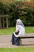 A Muslim woman wearing a headscarf sits on a park bench in London