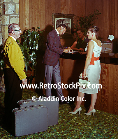 Couple checking in at the front desk. Bellman is helping with the suitcases. 1959 retro photograph.