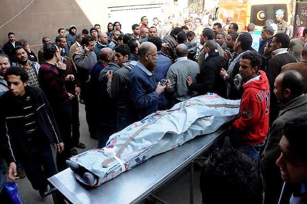 """EGY01 EL CAIRO (EGIPTO) 02/02/2012.- Decenas de personas alrededor del cadáver de una de las 74 víctimas de la tragedia ocurrida anoche en un estadio de fútbol en Port Said, antes de su traslado a un tanatorio en El Cairo (Egipto), hoy, jueves 2 de febrero de 2012. El primer ministro egipcio, Kamal Ganzuri, reconoció hoy su responsabilidad política por los disturbios de anoche en un partido de fútbol en Port Said y dijo que está dispuesto a rendir cuentas si se lo piden. """"Estoy dispuesto a cumplir con cualquier instrucción que me pida rendir cuentas, porque sé que soy responsable políticamente"""", dijo Ganzuri en un discurso ante el Parlamento, que hoy celebra una reunión de urgencia para analizar los sucesos. EFE/Str"""
