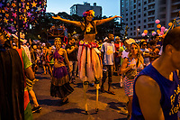 RIO DE JANEIRO, BRAZIL - FEBRUARY 23, 2014: A street performer dances as outpatients of the Instituto Philippe Pinel psychiatric hospital, their family and friends participate during the annual T&aacute; Pirando, Pirado, Pirou! carnival street parade on February 23, 2014 in Rio De Janeiro, Brazil. It looks like any of the other 450 or so street parties, locally called &ldquo;carnival blocks,&rdquo; that parade through Rio de Janeiro during the raucous pre-Lenten festivities that draw hundreds of thousands to the city each year. What makes this party different are its performers and organizers: psychiatric patients and their doctors, therapists, family members, neighbors and passers-by. The group, called T&aacute; Pirando, Pirado, Pirou!, which roughly translates as &ldquo;We&rsquo;re freaking out, we already freaked out!&rdquo;, began ten years ago when Brazil was in the process of dismantling its century-old system of mental asylums. A law passed in 2001 called for long-term outpatient psychiatric care to be offered primarily in community clinics. The number of such clinics increased more than fivefold in the following decade, while the number of asylum beds for psychiatric patients dropped 40 percent nationwide.<br /> <br /> Daniel Berehulak for The New York Times