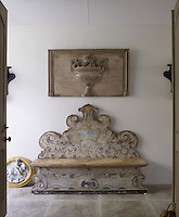In the entrance hall the curlicues of an ornately painted wooden bench are echoed in the carved relief hanging above