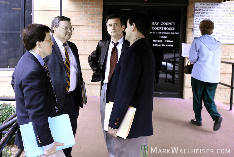 "Defense attorneys, from left,  Jonathan Dingus, James White, Waylon Graham, and Walter Smith have a ""meeting of the minds"" outside the door to the Bay Courthouse after the arraignment for the eight defendants in the Martin Lee Anderson case at the Bay County Courthouse in Panama City Thursday Jan. 18, 2007.  (Mark Wallheiser/TallahasseeStock.com)"