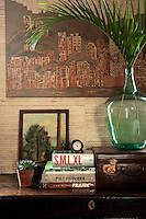 A home office, features a conglomerate of eclectic pieces and collectables giving the room an other-worldly, exotic feel. This theme is beautifully accentuated by a textured Philip Jeffries wallpaper made of split bamboo on grass cloth.