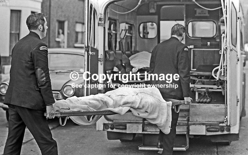 Ambulancemen take away the body of one of two policemen who were shot dead on 11th November 1971 by the Provisional IRA in an off-licence only 100 yards from Oldpark RUC Station in North Belfast. The police victims were later named as Constable Walter Moore, Londonderry, and Sergeant Dermot Hurley, originally from Wicklow in the Rep of Ireland. Sgt Hurley, a fluent Irish speaker, was the first Roman Catholic member of the RUC to be murdered in the Troubles. 19711110447c.<br /> <br /> Copyright Image from Victor Patterson, 54 Dorchester Park, Belfast, UK, BT9 6RJ<br /> <br /> t1: +44 28 9066 1296<br /> t2: +44 28 9002 2446<br /> m: +44 7802 353836<br /> <br /> e1: victorpatterson@me.com<br /> e2: victorpatterson@gmail.com<br /> <br /> www.victorpatterson.com<br /> <br /> IMPORTANT: Please see my Terms and Conditions of Use at www.victorpatterson.com