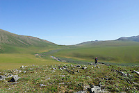 Jonathan Bennett walks toward the creek which defines Caribou Pass, above the Kongakut River, in Alaska's Arctic National Wildlife Refuge.