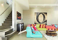 The large basement living room is furnished with funky low sofas that also double as a sleeping area for guests