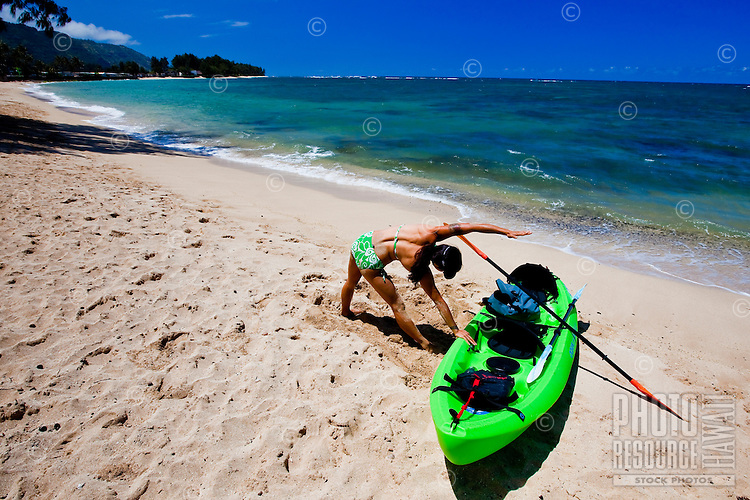 A young Asian woman stretching on the beach after paddling her kayak down the coast of Mokuleia