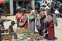 A group of women in traditional clothing survey vegetables for sale in Chajul market.
