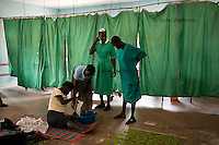 Nurses and a relative attend to a expecting mother sitting on the floor of the labor ward of Arua Hospital, Uganda.