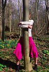ADFRY8 Young girl hugging a tree woodland in springtime