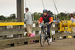 Dougie's Mitchell River Bridge. Chatham, MA. Woman cycling.