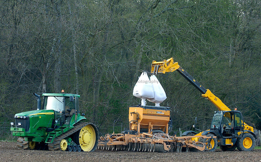 Photo: Richard Lane/Richard Lane Photography..A JCB telescopic fork lift truck lifts two tonne bags of seed into the hopper of a Simba Free Flow 6 metre seed drill, pulled by  John Deere 8420T tractor, sowing spring barley in a field in the Chiltern Hills near Beaconsfield, South Buckinghamshire. 09/04/2004.