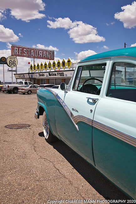 A two toned 1956 Ford Club Sedan gleams in the sun in front of  a period diner on Old Route 66 in Santa Rosa, New Mexico