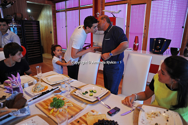 Ibrahim Ibrahimov (second from right) kisses his son Huseyn Ibrahimov, 18, as he arrives at the dinner table with Ibrahimov's granddaughter, Cahan Guliyeva, 4, in tow, as son Hasan Ibrahimov, 16, and daughter Ilkana Ibrahimova, 22, sit at the table in his home between Sangachal and Sahil, Azerbaijan on August 16, 2012.
