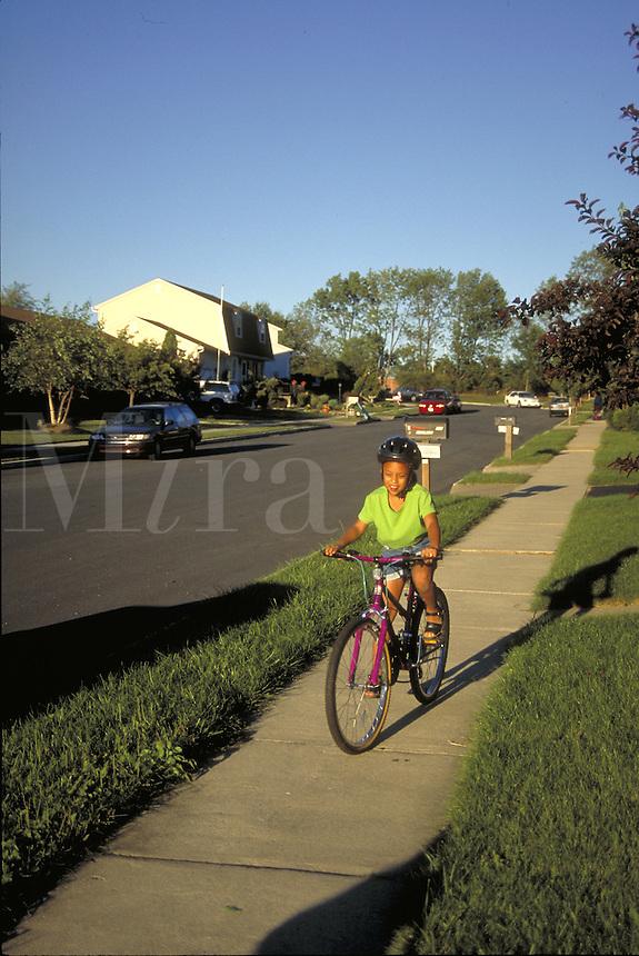 African-american girl riding bike in suburb.