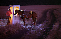 A cowboy talks on the phone in a telephone booth at night while his horse waits nearby.