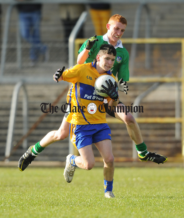 Cian O Dea of Clare in action against David Cussen of Limerick during their Munster minor championship semi-final at Cusack park. Photograph by John  Kelly.