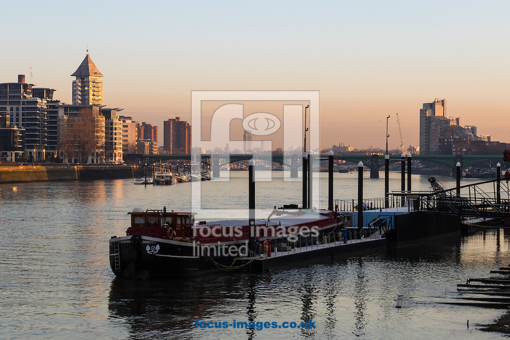 The early morning sun illuminates the distant buildings of Imperial wharf in Chelsea, as houseboats await the incoming tide on the River Thames, London <br /> Picture by Paul Davey/Focus Images Ltd +447966 016296<br /> 24/02/2016
