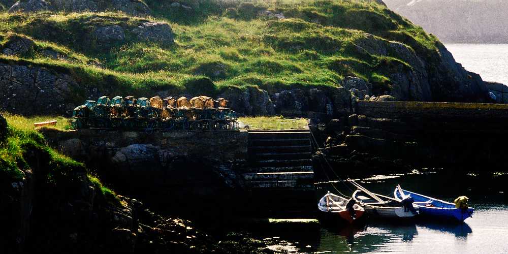 Stack of lobster traps and fishing boats. Ireland