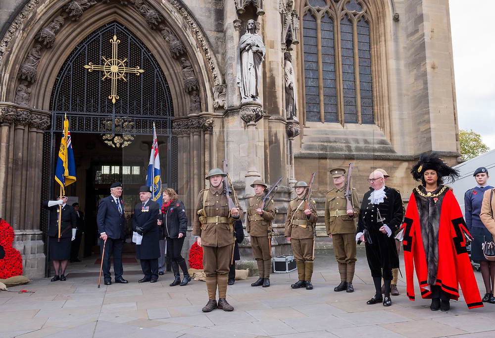 """© Licensed to London News Pictures. 27/10/2018. Bristol, UK. The Royal British Legion launch this year's Bristol Poppy Appeal, """"One thousand poppies, for one hundred years, for one million lives"""" at Bristol Cathedral. For the launch of the 2018 Bristol Poppy Appeal at 11am on 27 October, the Royal British Legion recreated a scene from the end of WW1 outside Bristol Cathedral on College Green, and Colonel Clive Fletcher-Wood read the war poem In Flanders Fields. They were joined by Civic Dignitaries Peaches Golding the Lord Lieutenant of Bristol, City of Bristol High Sheriff Mr Roger Opie (pictured), and Bristol's Lord Mayor Cleo Lake (pictured). A Bugler and the Bristol Military Wives Choir performed songs from their new album 'Remember'. Staff at MOD Filton filled 400 sandbags with eight tonnes of sand to build trenches and recreate 'Flanders Fields' and planted over 1000 waterproof poppies on College Green. Poppies and sandbags can be sponsored by individuals wanting to remember those who fought and died in conflict. There were re-enactors in WW1 uniform from Somerset Light Infantry (known as the West Country Tommys), as well as medics and nurses with equipment from the time. Bristol's own 'War Horse' (Buzz from Blagdon Horsedrawn Carriages) was on College Green behind the improvised barbed wire to represent the 350,000 horses that left Avonmouth for the frontline during WW1. There are also 10,000 knitted poppies on display both in and outside Bristol Cathedral following 'The Charfield Yarn Bombers' incitement to locals to get knitting to mark the occasion, with a display inside the Cathedral organised by Helen Date. Photo credit: Simon Chapman/LNP"""