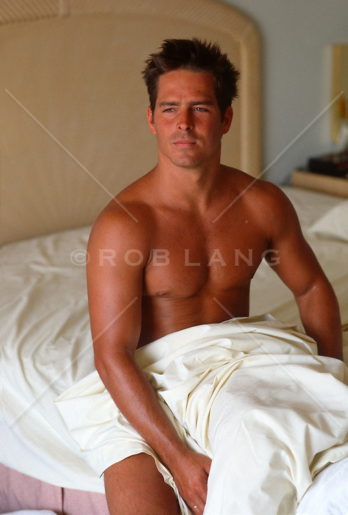 Shirtless man wrapped in a bedsheet sitting up in bed