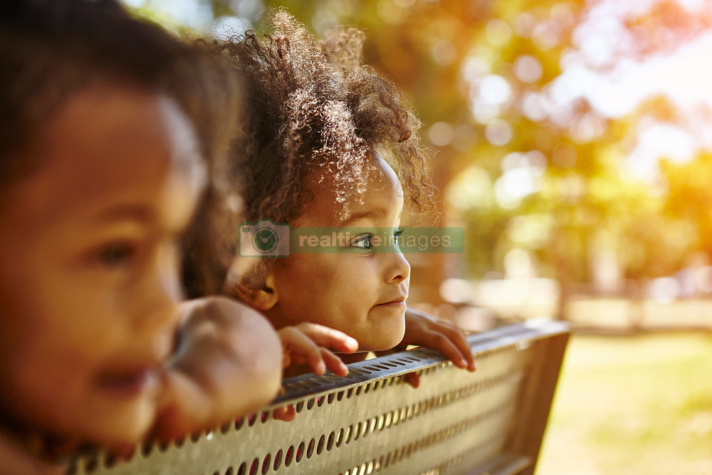 February 19, 2017 - Two young sisters looking peering over bench (Credit Image: © Cultura via ZUMA Press)