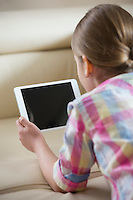 Rear view of girl using tablet PC at home