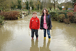 © Licensed to London News Pictures. 25/11/2012. Malmesbury, UK. Picture of Cian aged 8 and Erin aged 11 (parent did not give surname) wading through flooding in the centre of Malmesbury.  25 November 2012..Photo credit : Simon Chapman/LNP