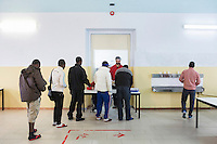 CALTANISSETTA, ITALY - 28 NOVEMBER 2014:  Asylum seekers line up for lunch at the the Pian del Lago CARA (Accommodation Centre for Asylum Seekers) in Caltanissetta, Italy, on November 28th 2014. To this date, the Pian de Lago CARA hosts 491 asylum seekers, while 40 illegal immigrants are held in the CIE (Center for Identification and Deportation), before being deported.