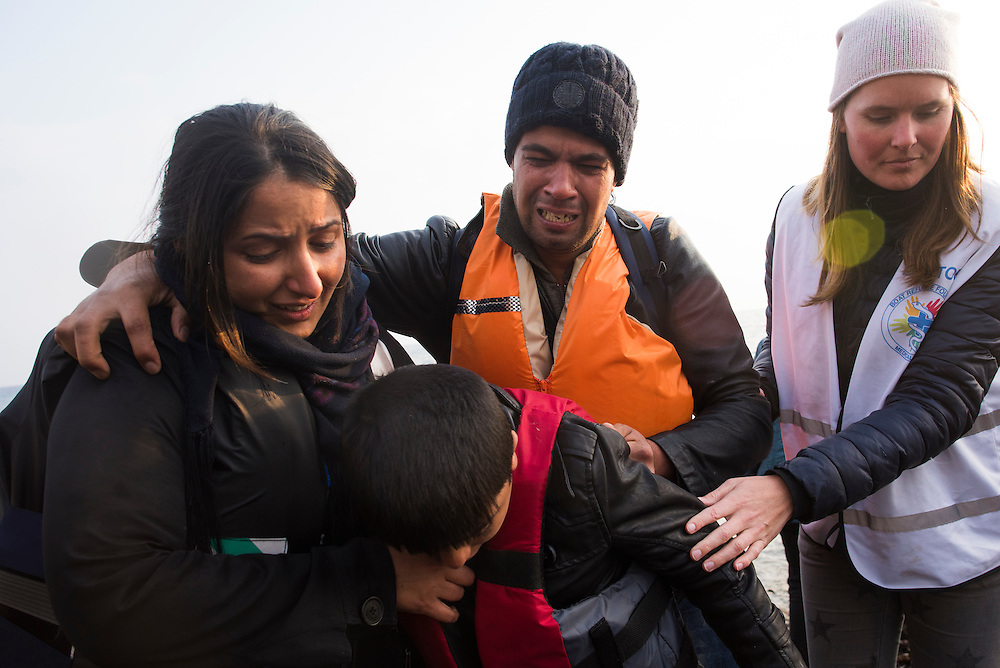 An emotional family is assisted by a volunteer as they arrive on Lesbos Island on March 20, 2016 near Mitilini, Greece.