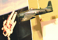 A model plane hangs in Anderson's studio near a picture of an astronaut in space.  Photo by Elliot Knight