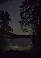 Seven participants and two guides led a Wilderness Inquiry canoe adventure on Brule Lake in the Boundary Waters from Sept. 5 to September 9, 2012...With some help light painting, a night scene was captured of the stars included the surrounding trees.