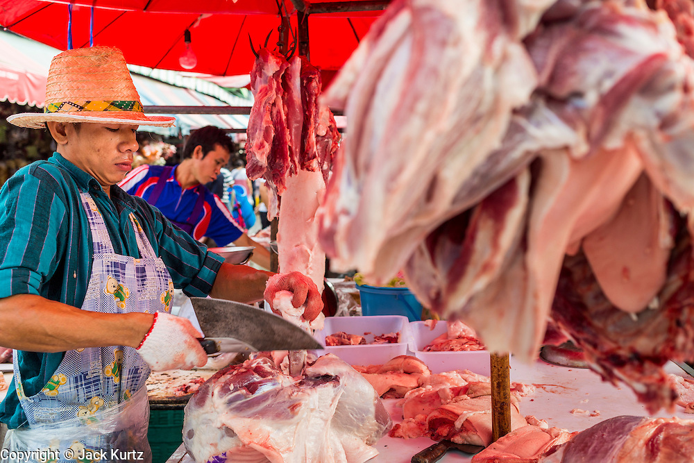 "24 AUGUST 2013 - BANGKOK, THAILAND: A meat cutter trims cuts of pork in Khlong Toei Market in Bangkok. Thailand entered a ""technical"" recession this month after the economy shrank by 0.3% in the second quarter of the year. The 0.3% contraction in gross domestic product between April and June followed a previous fall of 1.7% during the first quarter of 2013. The contraction is being blamed on a drop in demand for exports, a drop in domestic demand and a loss of consumer confidence. At the same time, the value of the Thai Baht against the US Dollar has dropped significantly, from a high of about 28Baht to $1 in April to 32THB to 1USD in August.    PHOTO BY JACK KURTZ"