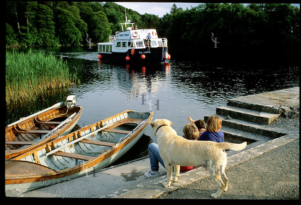 Kids & dog sit on dock as tour boat returns to Ashford Castle on Lough Corrib at sunset; Cong. Ireland