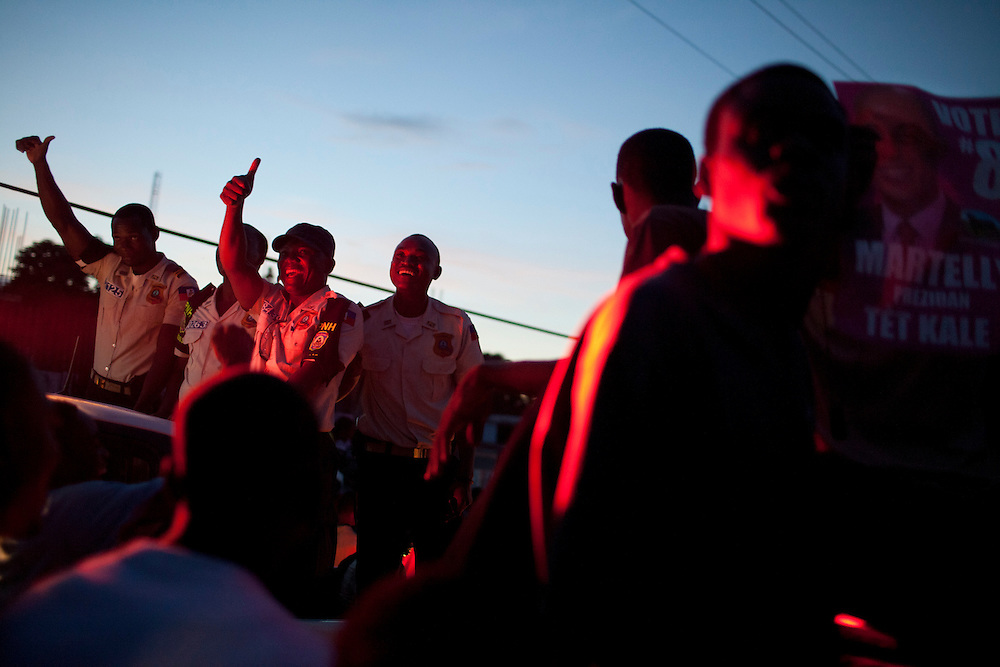 Police officers give a thumbs up as singer Wyclef Jean and Haitian presidential candidate Michel Martelly pass by on top of a truck during an impromptu election protest on November 28, 2010 in Port-au-Prince, Haiti.