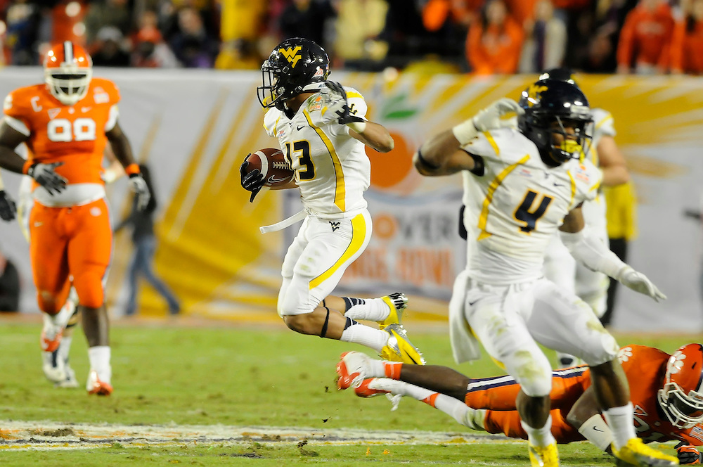 January 4, 2012: Andrew Buie #13 of West Virginia hops over Rashard Hall #31 of Clemson during the NCAA football game between the West Virginia Mountaineers and the Clemson Tigers at the 2012 Discover Orange Bowl at Sun Life Stadium in Miami Gardens, Florida.