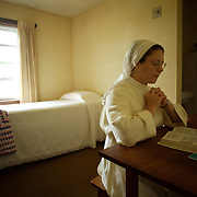 "Sister Michele Armstrong spends time each day reading and praying in her small ""cell"" or room at Our Lady of the Mississippi Abbey, a monastery of Trappist nuns.  ""This is a private place where I feel like I'm entering the tomb of Jesus and the womb of Jesus,"" she says about her tiny room.   The community of 22 Roman Catholic women follow Jesus Christ through a life of prayer, silence, simplicity and ordinary work.  Their home is a beautiful monastery which sits high on a bluff, overlooking the Mississippi River."