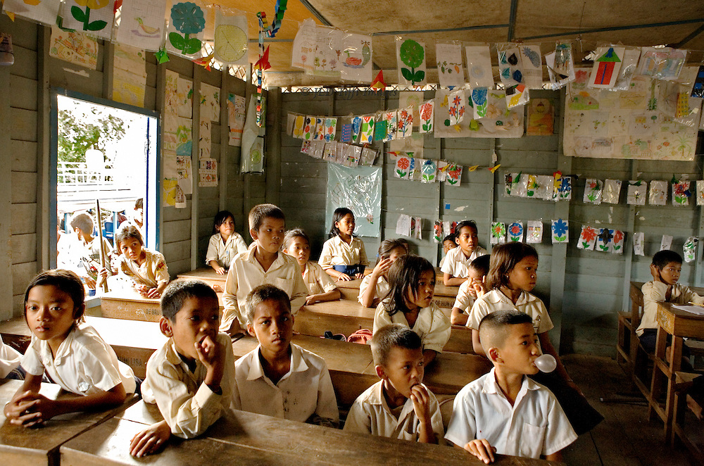 Tonle Sap lake : schoolroom with children (boys and girls ) ; one boy blowing bubble gum.