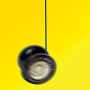 Digitally enhanced image of a spinning black and white yoyo on yellow background