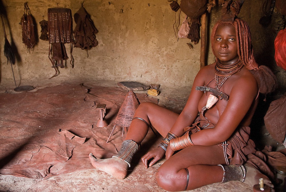Himba woman in her hut in a village near Epupa Falls, Namibia, Africa.