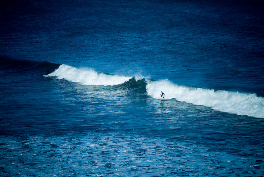 A lone surfer on a white wave