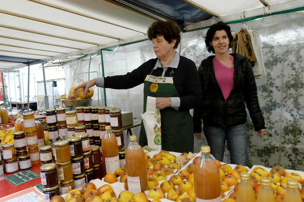 Evelyne Nochet, owner of the Nouveau Verger apple orchard in the Loire valley, and her daughter Marina selling ancient apple varieties at thier stand in the Marché Mouton-Duvernet. .Paris, France. 19/06/2009..Photo © J.B. Russell