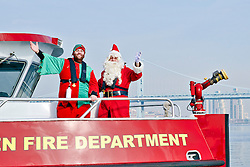 At his arrival in the region, Scuba Santa tours Philadelphia and visits local touristic attractions. The trip brings Scuba Santa and his helper, Elffish from 30th Street station via City Hall and Independence Mall to Penn's Landing where he and his helper board for Camden. The fire boat of the Camden Fire Dept. brings them to the other side of the Delaware River where a Ladder and Engine are waiting for the final stretch of the trip towards the Ocean Realm theater of the Adventure Aquarium...