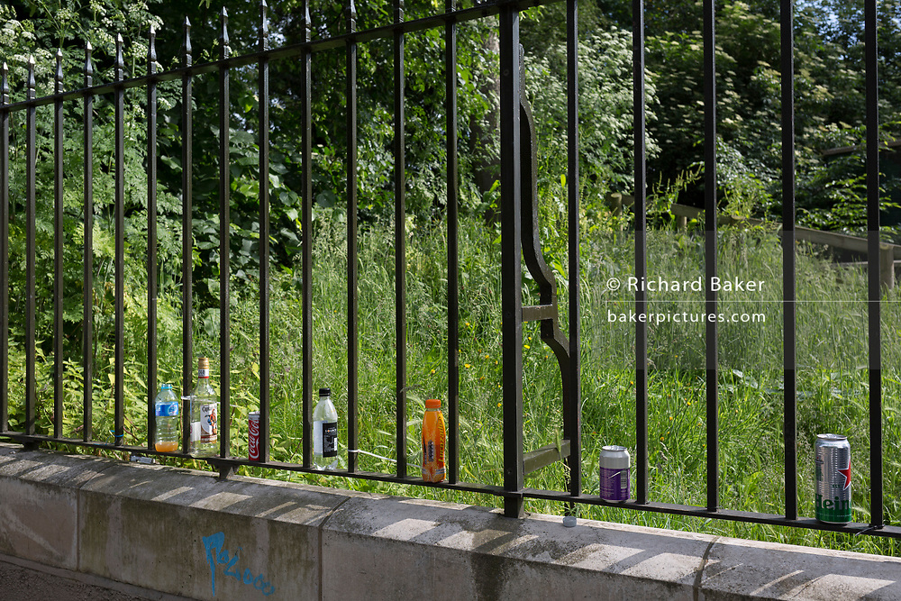 Discarded dink cans and bottles lined up on the railings bordering Brockwell Park during Field Day Festival on 1st June 2018, in the London borough of Lambeth, England.