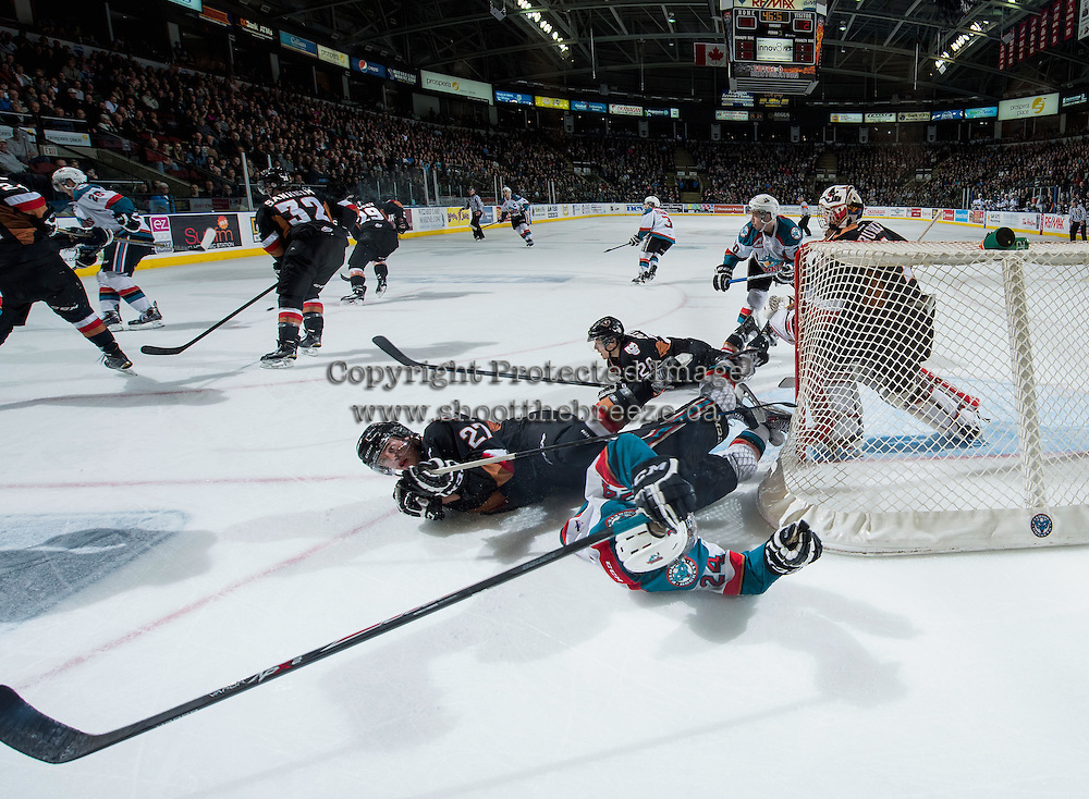 KELOWNA, CANADA - FEBRUARY 28: Tyson Baillie #24 of Kelowna Rockets falls to the ice after being checked by Ben Thomas #27 of Calgary Hitmen on February 28, 2015 at Prospera Place in Kelowna, British Columbia, Canada.  (Photo by Marissa Baecker/Shoot the Breeze)  *** Local Caption *** Ben Thomas; Tyson Baillie;