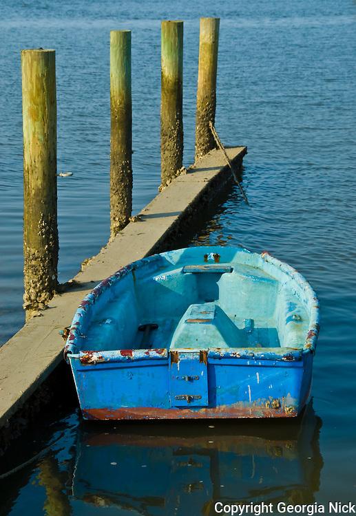 A blue dinghy rest against a finger pier on Salt Run in historic St. Augustine, Florida.
