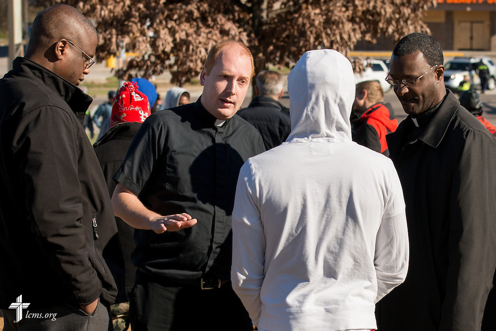 (L-R) Vicar Chris Chandler of Concordia Seminary, St. Louis, the Rev. Adam Filipek, pastor of Salem Lutheran Church in Black Jack, Mo., and the Rev. John Lewis, pastor of St. Matthew Lutheran Church in St. Louis, talk to a protestor in Ferguson, Mo., on Tuesday, Nov. 25, 2014. LCMS Communications/Erik M. Lunsford